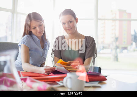 Portrait of young businesswoman with female colleague discussing over fabric swatches in office - Stock Photo