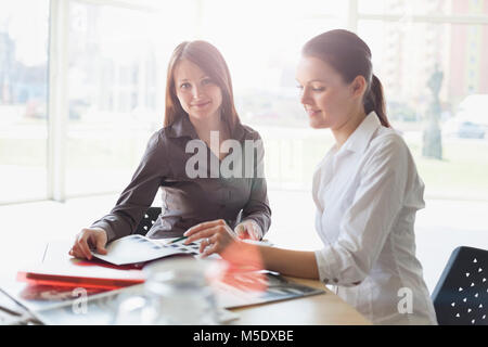 Portrait of young businesswoman with female colleague discussing at desk in office - Stock Photo