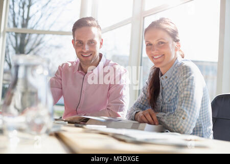 Portrait of smiling young business people in meeting room - Stock Photo