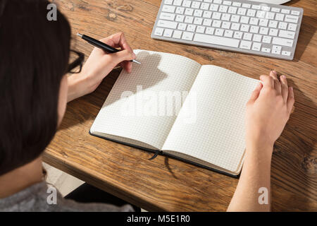 Close-up Of A Businesswoman Writing On Checker Note Book With A Pen At Workplace - Stock Photo