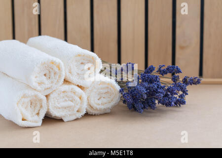 Beige bath towels on wooden background and a bunch of dried lavender. Spa concept - Stock Photo