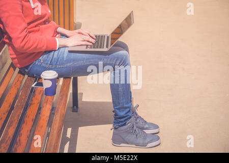 Female hands on laptop keyboard. She is sitting on bench outdoors. Coffee to go next to her. Technology and modern - Stock Photo