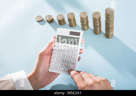 Person Calculating Savings On Calculator And Stacked Coins On Blue Desk - Stock Photo
