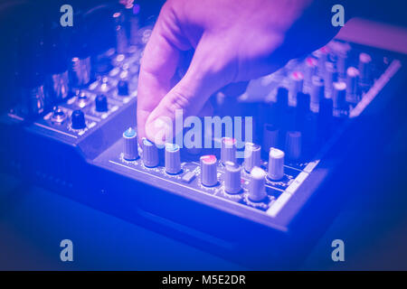 Close up of hand using studio sound equipment - Stock Photo