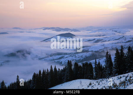 The fog covers the valley at dawn. Carpathians, winter. - Stock Photo