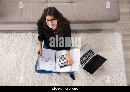 Elevated View Of A Woman Sitting On Rug Calculating Bills Using Calculator At Home - Stock Photo