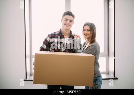 home, people, repair and real estate concept - happy couple holding cardboard boxes and moving to new place - Stock Photo