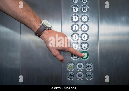 Male forefinger pressing the zero floor button in the elevator. Iron made interior. - Stock Photo