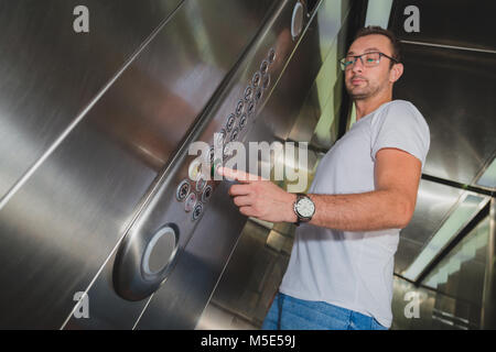 Young man in elevator pressing the zero floor button. Iron made interior. - Stock Photo