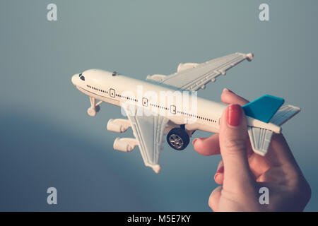 Woman holding airplane model. Travel, vacation and air transportation concepts. - Stock Photo