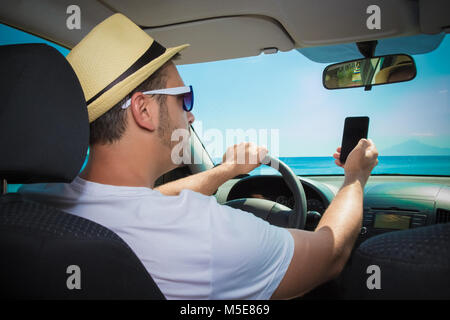 Tourist guy using cell phone during the drive. - Stock Photo