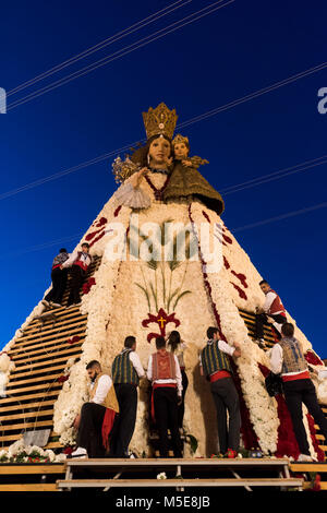 People placing all the flower offerings brought to the Virgin Mary during 'La Ofrena' procession as part of the - Stock Photo