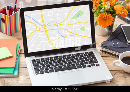 GPS, navigation. Map on a computer screen on a wooden office desk - Stock Photo