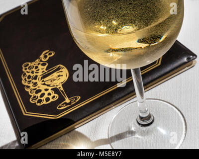 Glass of chilled white wine on sunlit alfresco restaurant table with wine list menu behind - Stock Photo