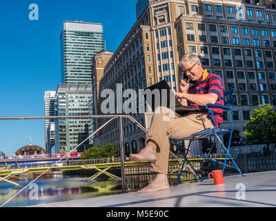 Relaxed mature self employed businessman outside on his office boat talking on iPhone smartphone working at a laptop - Stock Photo