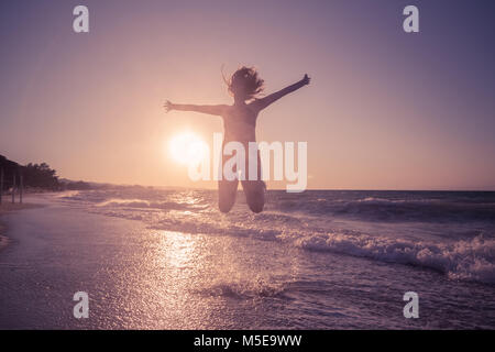 Silhouette of female jumping on beach. Waves and sunset over sea in the background. Summertime concept. - Stock Photo
