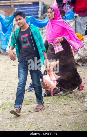 A young boy and his Mother is returning home after purchasing a fish from the fair (Poradah Mela) for the family. - Stock Photo