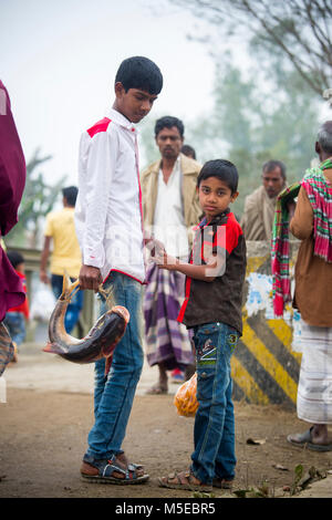 A young boy and his little brother is returning home after purchasing a fish from the fair (Poradah Mela) for the - Stock Photo