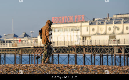 Brighton UK 23rd February 2018 - A metal detectorist strolls along Brighton beach on a beautiful sunny but cold - Stock Photo