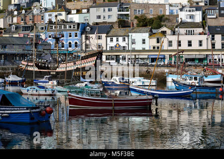 View of boats in Brixham Harbour including Golden Hind, Heritage Vessel 'IRIS' and True Vine with harbourside shops - Stock Photo