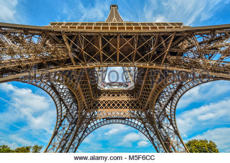 View looking up from underneath the Eiffel Tower on a sunny day with powder blue skies in Paris France - Stock Photo