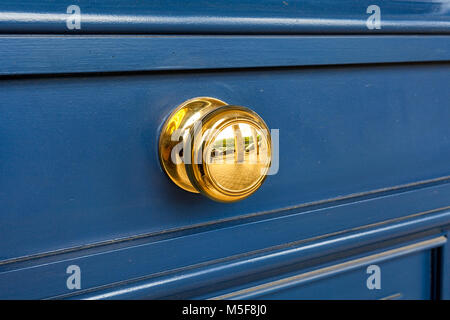 Rounded yellow handle on wooden door in Paris, France. - Stock Photo