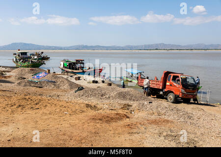 Bagan, Myanmar, December 27 2017: Workers load sand on ship at the jetty of the irrawaddy river - Stock Photo