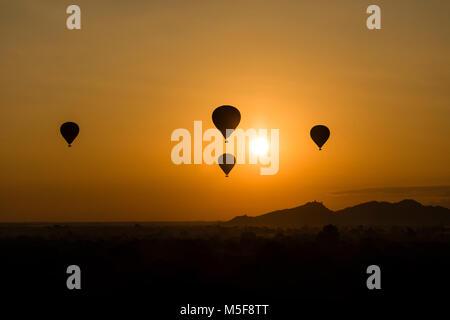 BAGAN, MYANMAR, JANUARY 2, 2018: Scenic sunrise with many hot air balloons above Bagan in Myanmar. - Stock Photo