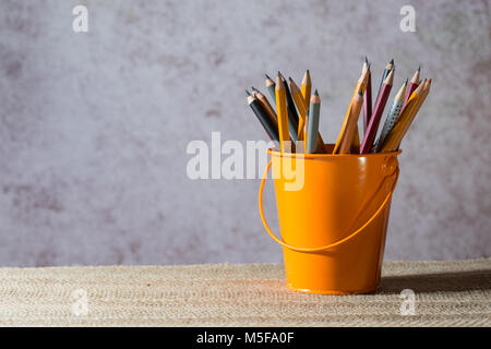 A set of colored pencils on a toy bucket in a beautiful brownish background - Stock Photo