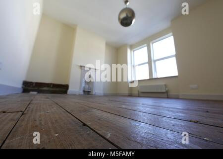 Old bare floorboards in an empty bedroom in a victorian terraced house. - Stock Photo