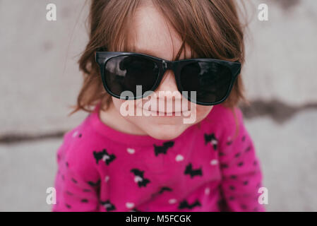 A toddler girl wearing a pink shirt and sunglasses, standing on a sidewalk on a warm, sunny day. - Stock Photo