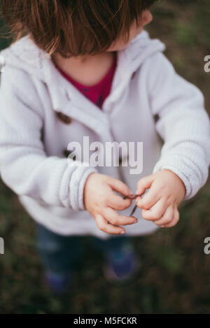 A toddler girl holds a worm in her hands on a cool spring day. - Stock Photo