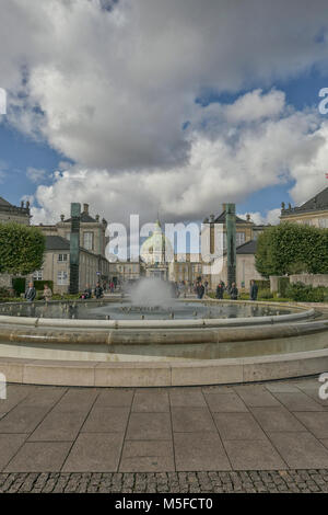 COPENHAGEN, DENMARK - OCT 3,2017 Fountain, statue and dome of the Marmor Cathedral form a line in Amalienborg - Stock Photo