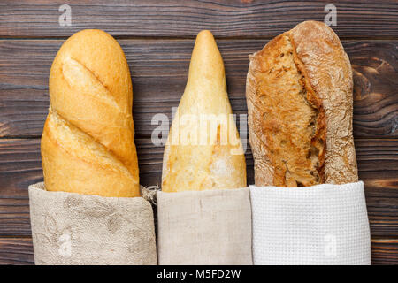 Loaf of bread in a bag european style on a rustic table. - Stock Photo