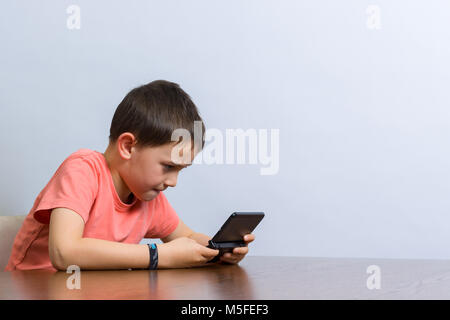 Young boy playing handheld video game at a table. Against grey background - Stock Photo