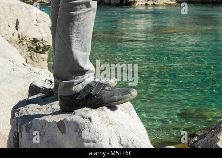 Adult man standing on a rock near the turquoise river. Concept - relaxing in the nature - Stock Photo