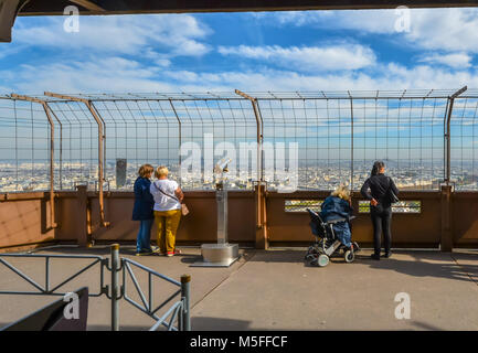 Tourists including a woman in a wheelchair enjoy the city view of Paris on a sunny day from the first platform of - Stock Photo