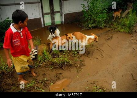 Indonesia. 23rd Feb, 2018. a child with his pet dog, was trying to cross a cold lava track filled with mud in the - Stock Photo