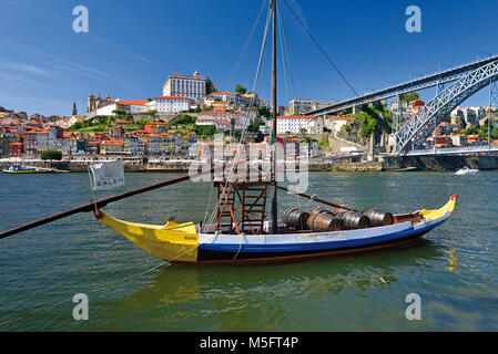 Traditional port wine ship in river Douro with Oporto in the background - Stock Photo