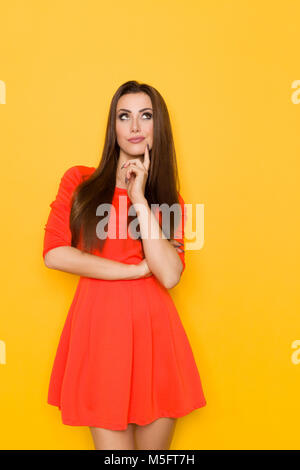 Beautiful young woman in red mini dress is holding hand on chin, looking up and grimacing. Three quarter length - Stock Photo