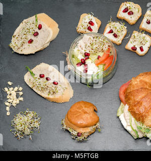 healthy food, menu with microgreens. Vegetarian sandwiches with micro greens assortment. Vegan party food table - Stock Photo