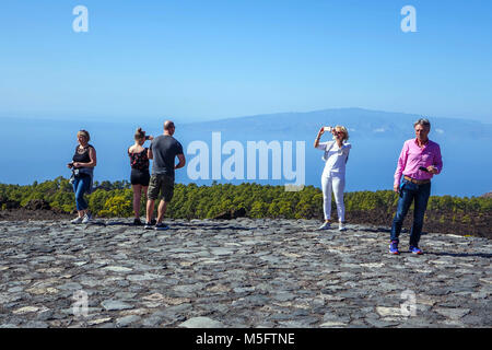 Tourists on Tenerife taking photographs and selfies with mobile phone, El Tiede, National Park - Stock Photo