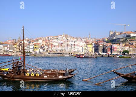 Douro River waterfront in Gaia with Barrio La Ribeira across river and Rabelo Boats, Porto, Porto Region, Portugal - Stock Photo