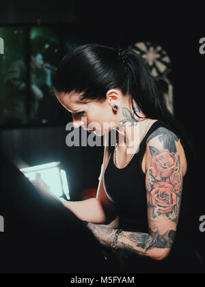 Close up of artist demonstrates the process of getting black tattoo with paint. Master working in workshop. Tattooing - Stock Photo