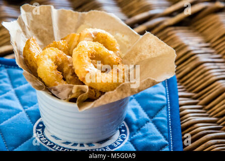 Fried calamari rings and chips, top view macro photo, food photography. Fish and chips in paper, white dish, blue - Stock Photo