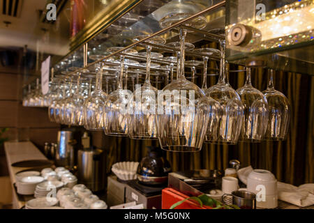 Wine glasses hang above the bar in a hotel. - Stock Photo