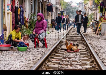 Chinese tourists walk along 'Hanoi Train Street', a narrow street in the centre of Hanoi with live railway tracks - Stock Photo