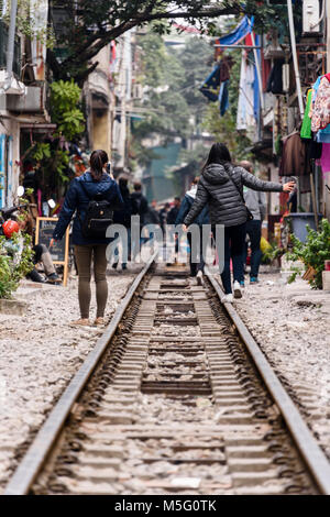 Chinese tourists walk along 'Hanoi Train Street', a narrow street in the centre of Hanoi with live railway tracks - Stock Photo