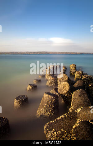Concrete Sea Defences in the form of four legged tetrapods with stunning view of sea and land opposite on horizon. - Stock Photo