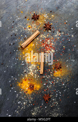 Artistic colorful background of a variety of spices on slate - Stock Photo